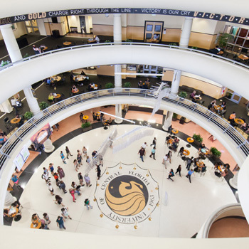 downward shot of inside the student union from top floor, focus on pegasus logo, students walking by