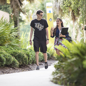 male and female ucf students walking around campus, surrounded by trees and plant life