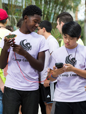 two highschool students wearing ucf shirts working together on science project