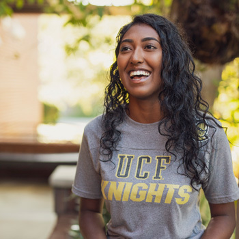 female ucf student wearing grey ucf knights t shirt, curly hair, smiling and look off camera to her right