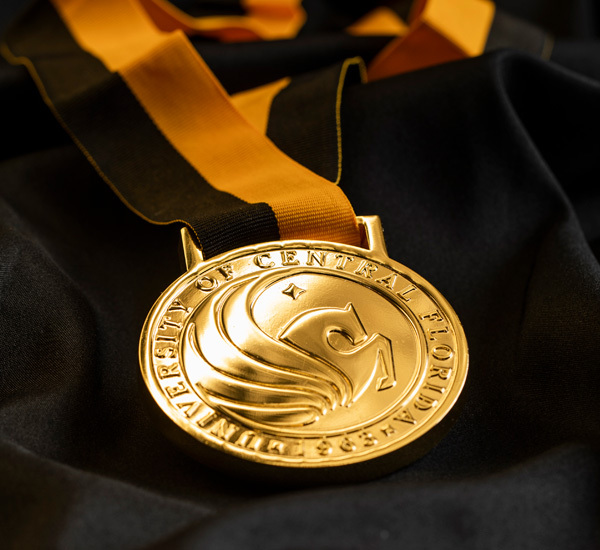 image of national merit scholar pendant and ribbon necklace on top of black satin-looking background