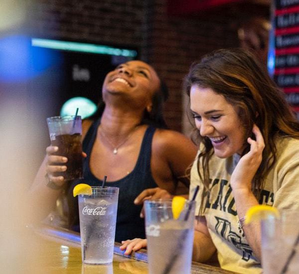 two female sutdents sitting at bar drinking water and soda, laughing and having fun on campus