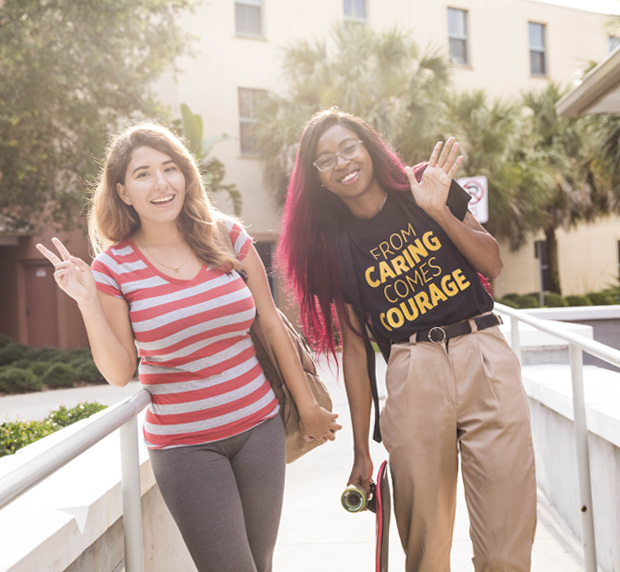 two female students standing and posing for the camera, leaning to their right waving and showing a peace sign with their fingers