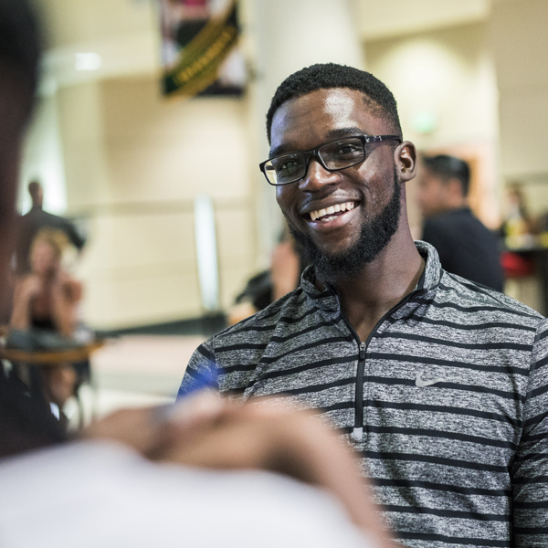 male ucf student in glasses and a black and grey striped polo, smiling at someone to the left of camera