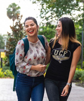 two female students with dark hair, walking outside while laughing