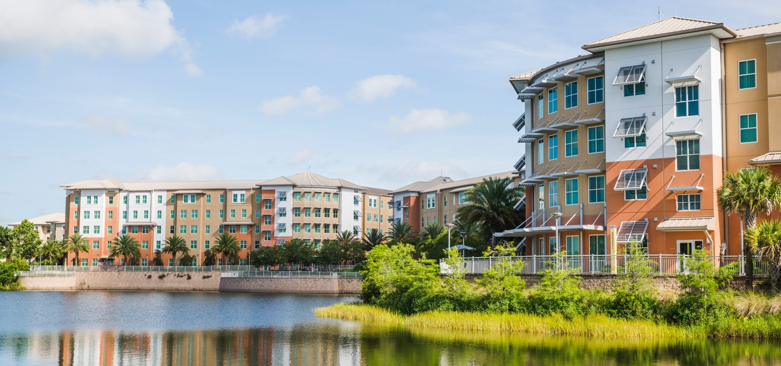 image of ucf housing towers at knights plaza, view from over a lake