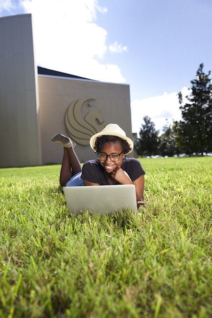 Student using computer in grass outside Welcome Center