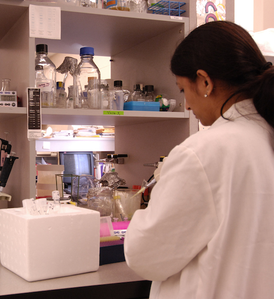 female student in white lab coat working in a lab