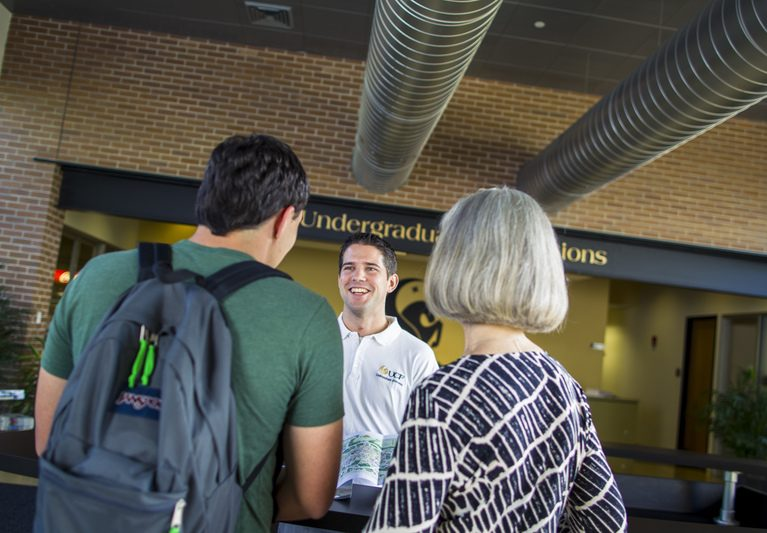 mom and backpack-wearing son with backs to camera, talking to ucf undergraduate admissions employee, looking at map together