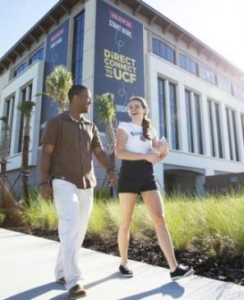 a male and female student walk by direct connect to ucf sign on campus building