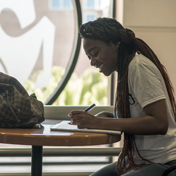 female ucf student filling out admissions forms at a table in front of glass etched pegasus logo
