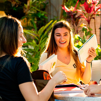 two females applying to ucf at an outside table while smiling