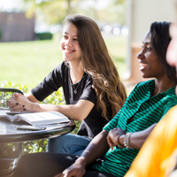 2 female ucf students laughing while sitting outside at a table with books open