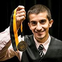 Burnett Honors College Student holding honors medallion