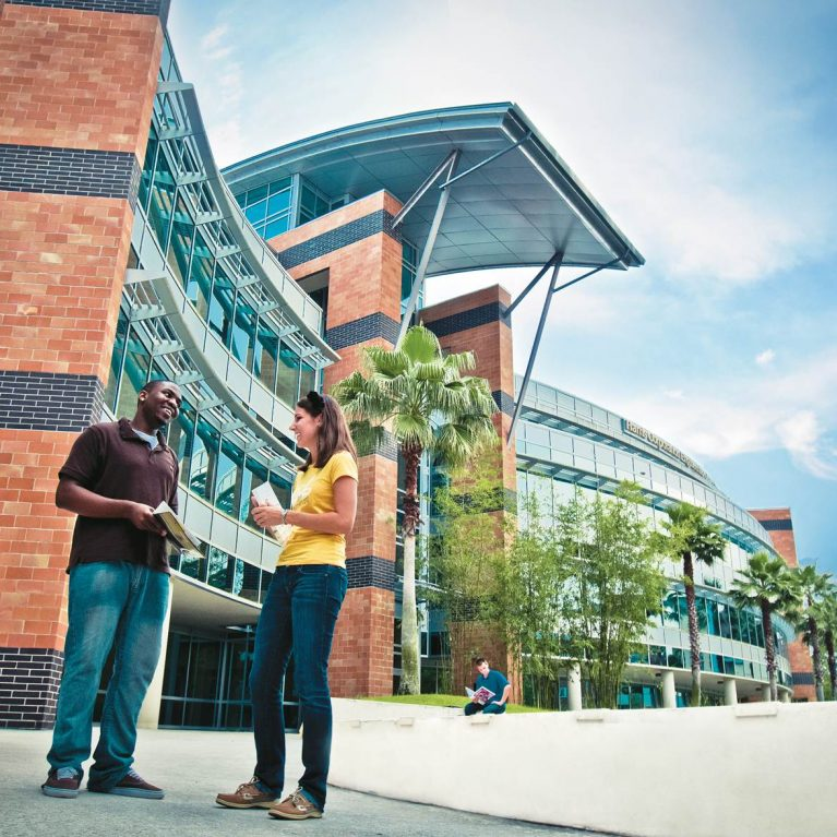 A photo of the Harris Engineering building at UCF. There are two students talking to each other outside of the entry.