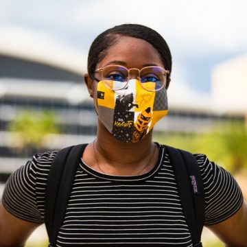 female ucf student wearing ucf-themed mask