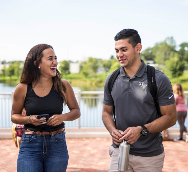 A male and female student are walking on a brick courtyard near a pond. They are talking and laughing.