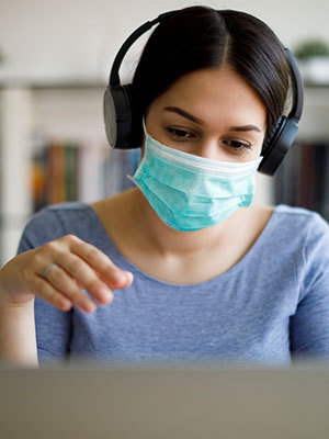 woman wearing mask and headphones reading notes