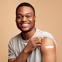student showing arm with Band-Aid after getting COVID-19 vaccine