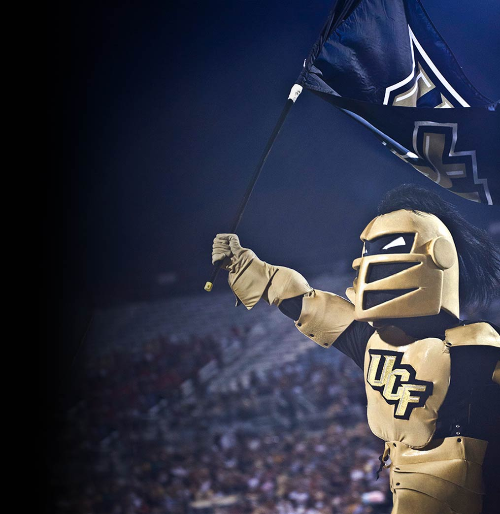 knightro holding the ucf flag before a ucf football game