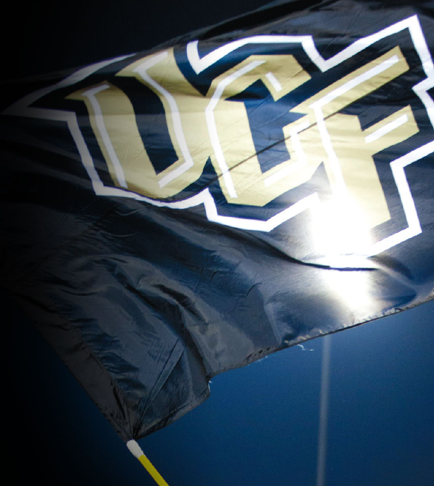 black flag with gold and whilte letters spelling UCF, flying in front of a football stadium light