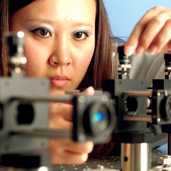 closeup of female's face while working intensely in optics and photonics lab