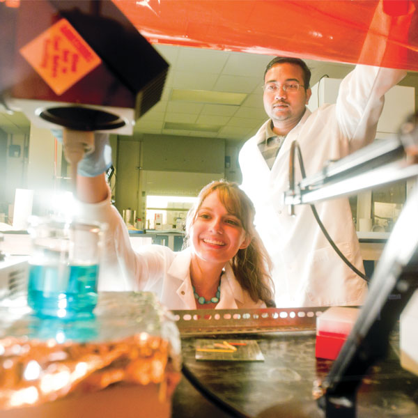 male and female ucf students in white lab coats working in a lab