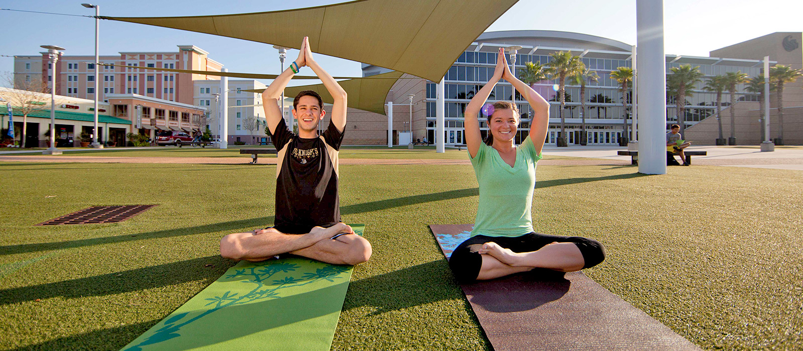 two students doing yoga at ucf