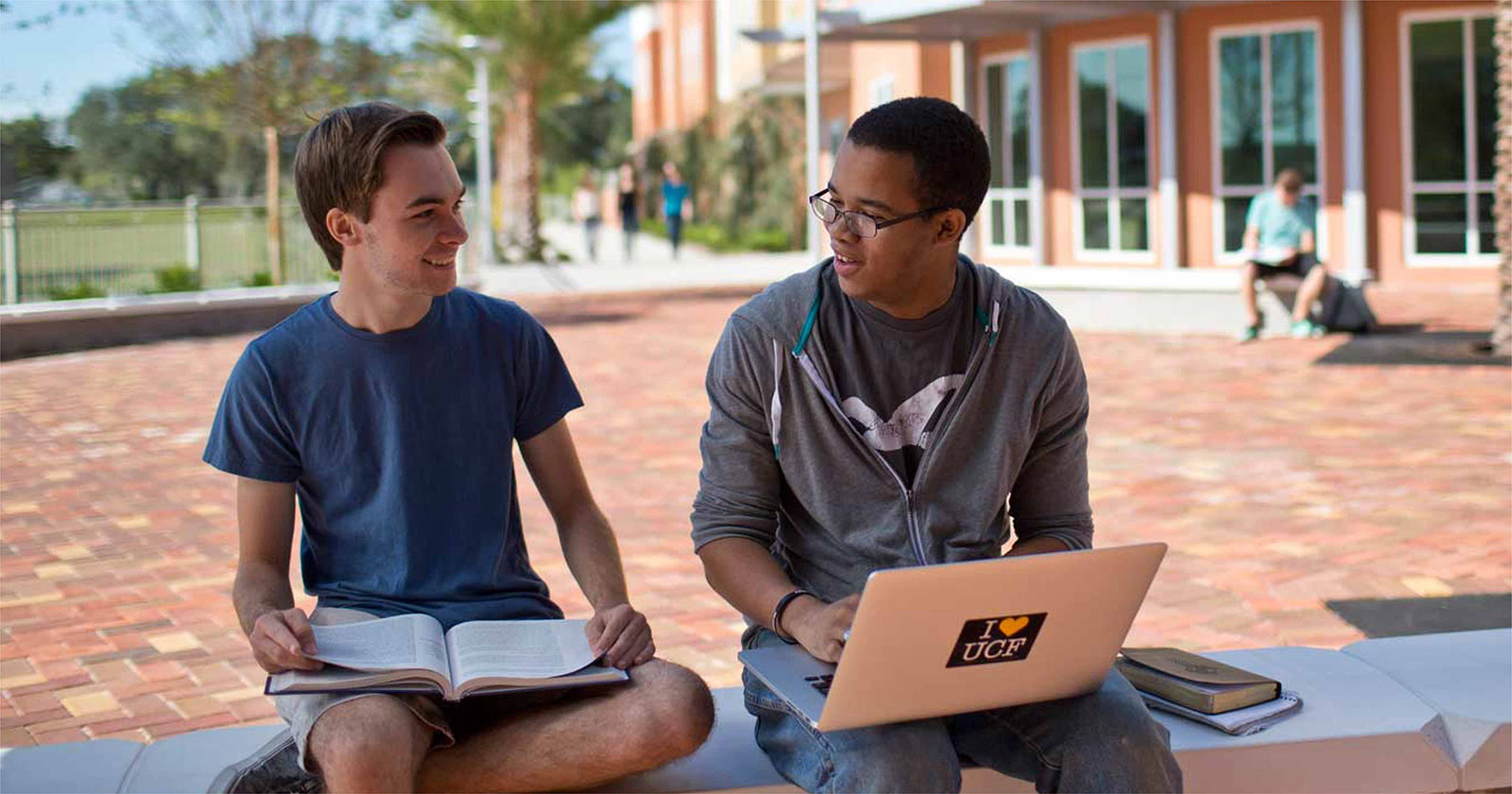 two ucf students sitting outside on a bench studying together