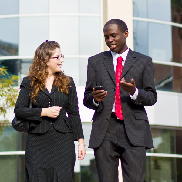 male and female professionals walking and talking outside of ucf building