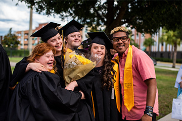Five graduates from UCF's Inclusive Education Services taking a celebratory photo together after graduating