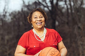 Marcie (Swilley) Washington is pictured smiling while standing outside holding a basketball