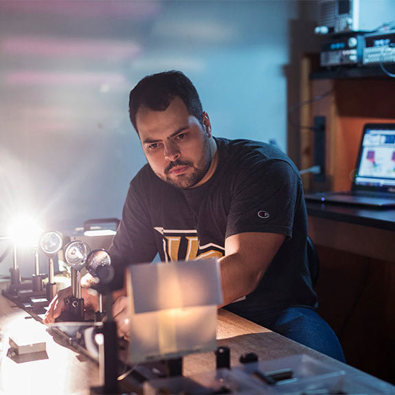 male ucf student working in optics and photonics lab