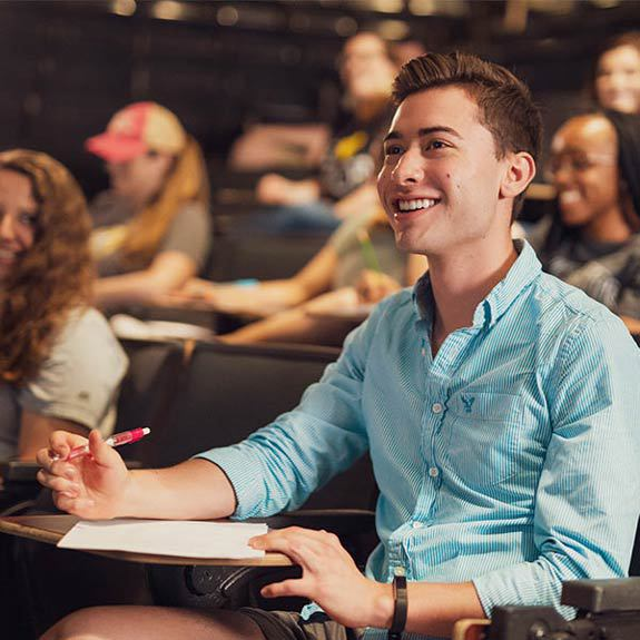 male ucf student learning in classroom