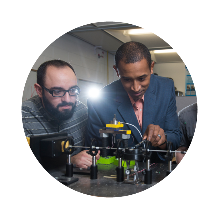 Professor helping students with mechanical engineering project