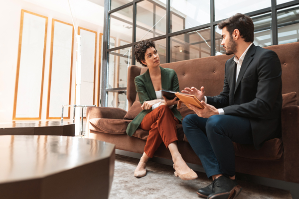 two individuals seated on a couch talking about business