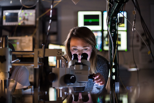 female looking into microscope