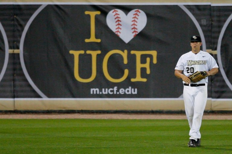 """UCF Baseball player standing in front of banner """"I (heart) UCF"""""""