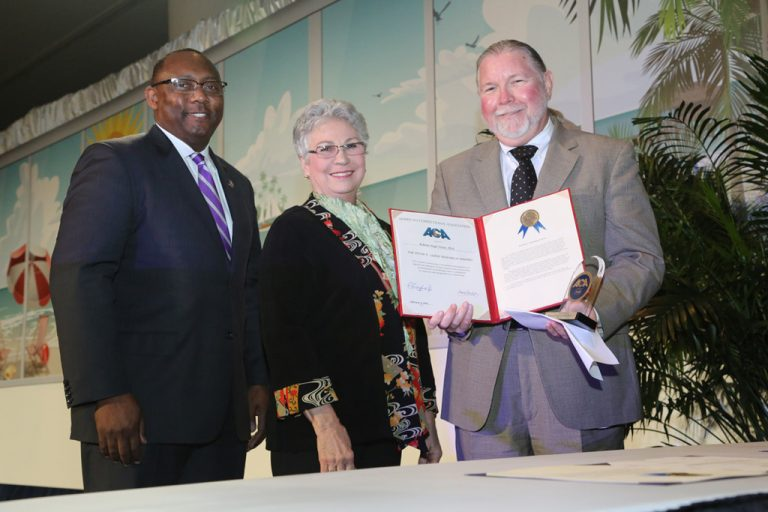 Christopher Epps, president of the American Correctional Association, and Betty Adams Wooten, chair of ACA's Correctional Awards Committee, presented the Lejins Award to Professor Roberto Hugh Potter.