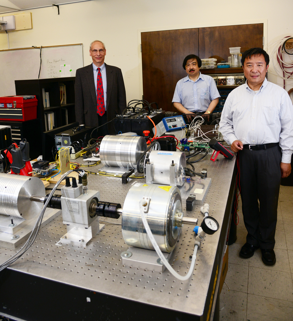 From left, Maglev Chief Financial Officer Martin Epstein and UCF College of Engineering & Computer Science Professors Louis Chow and Thomas Wu  with research equipment in Wu's lab.