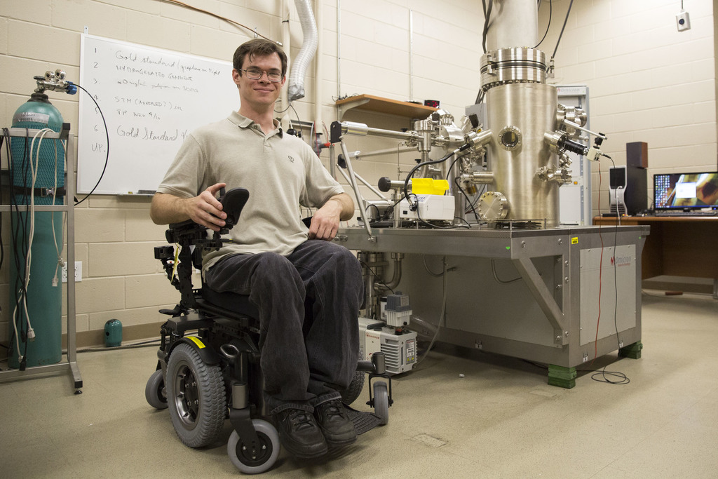 Doctoral student Michael Lodge received a wheelchair with a seat lift, enabling him to see into the electron microscope where he conducts research. Photos by Lauren Haar/UCF