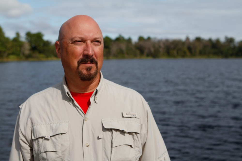 bald man with mustache and khaki button down with red shirt underneath standing by the water with trees in the background