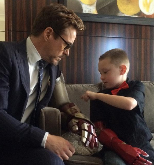 man with bionic arm talks to little boy with bionic arm