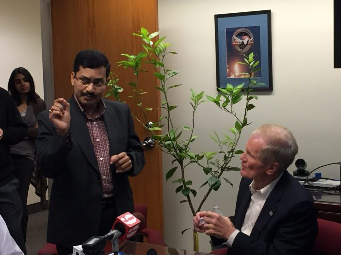 UCF professor Swadeshmukul Santra, left, explains his research into curing citrus greening at a news conference with U.S. Sen. Bill Nelson, right.