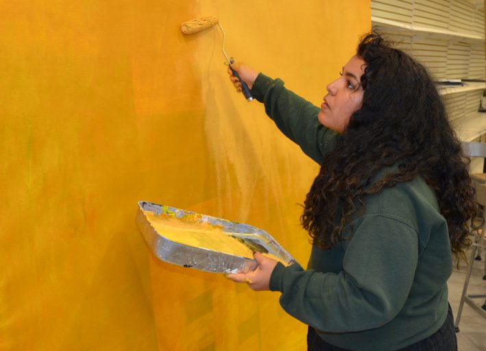 Adryanna Rivera-Delgado, a senior studio art major, works on the early stages of recreating a Gustav Klimt painting for the tableau vivant exhibit.