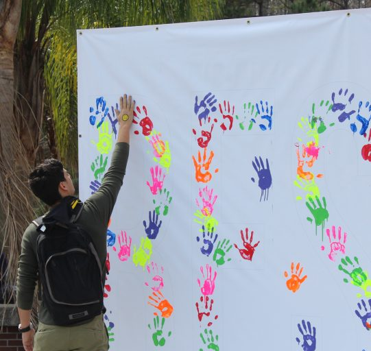 student puts paint handprint on white sheet along with others