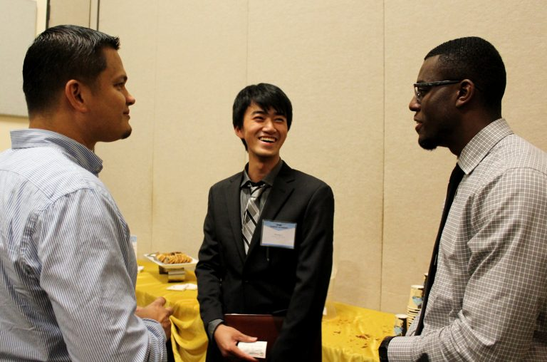 Electrical engineering majors Brandon Carty and Jihang Li discuss job options with Felix Lugardo of Power Grid Engineering, a national firm with an office in Lake Mary. (Photo by Clara Winborn)