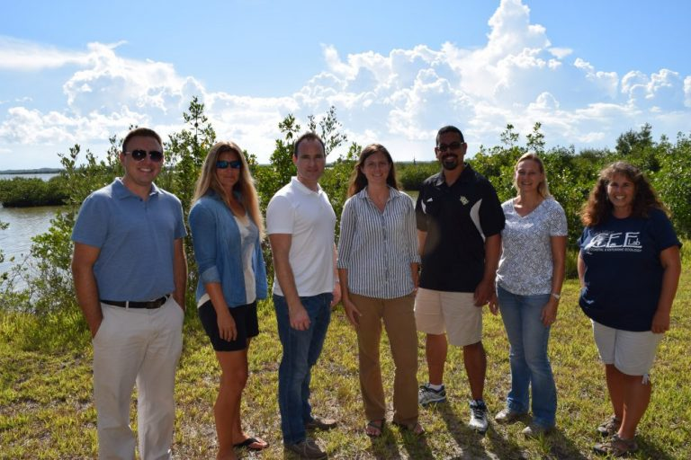 group of 6 people standing side by side smiling at the camera, while they are outside