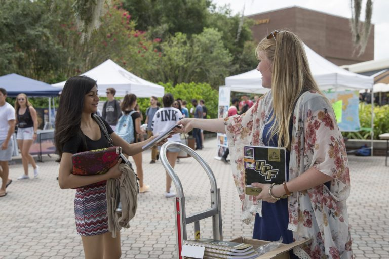 woman handing student pamphlets by the student union