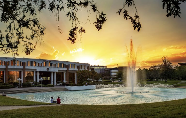 side angle photo of millican hall and the reflecting pond at sunset with the sky vibrant yellow and oranges